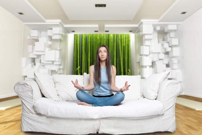 Frau meditiert auf dem Sofa