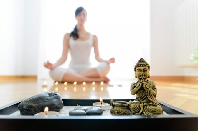 Im Hintergrund ist eine meditierende Frau zu sehen, im Vordergrund eine Buddha-Figur und Kerzen