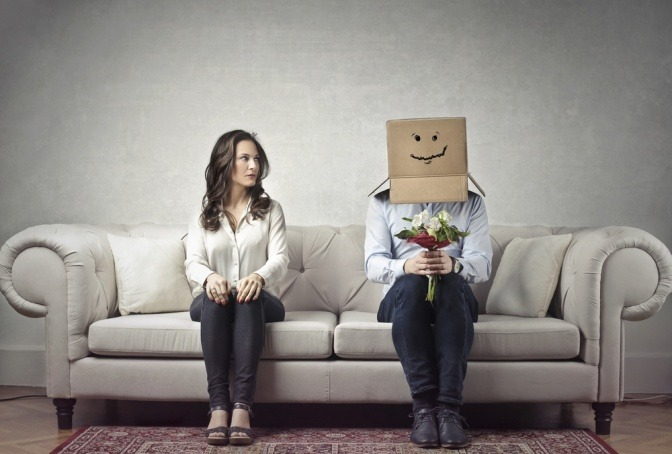 Frau und Mann mit Papiertüte auf Sofa, zwischen ihnen besteht keine Beziehung aber mehr als Freundschaft.