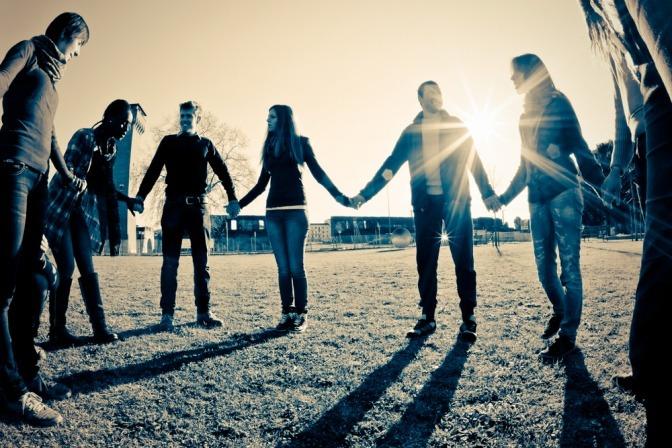 Eine Gruppe von Menschen die einander an der Hand halten