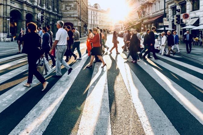 Viele Menschen überqueren eine Straße auf einem Zebrastreifen
