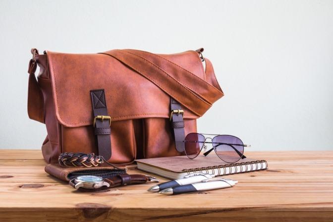 Neben einer Messanger Bag liegen Stifte und Zetteln