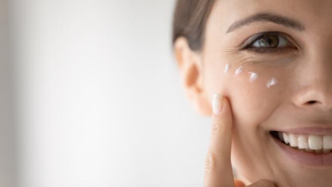 Junge Frau mit Creme auf der Gesichtshaut zum Vorbeugen von Pickeln