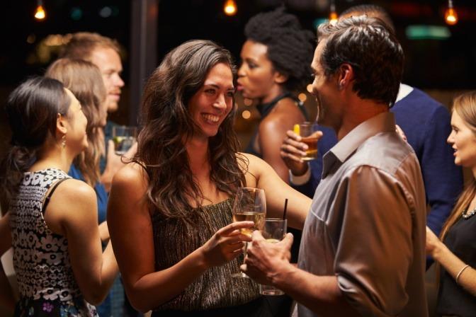 Eine Frau und ein Mann tanzen und flirten ausgelassen bei einer kleinen Feier