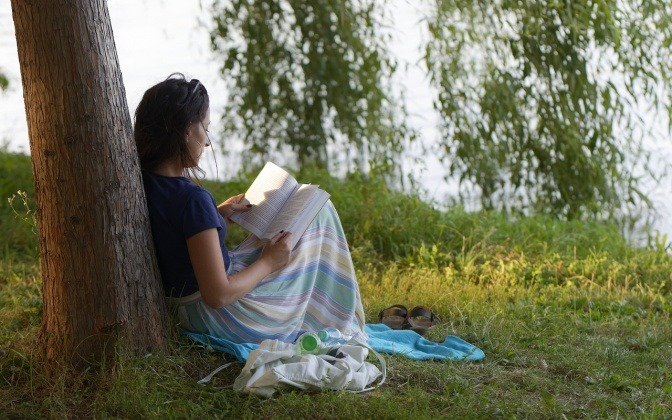 Eine Frau, die Minimalismus mag, liest in der Natur