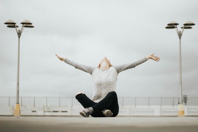 Eine Frau sitzt auf einer Straße und streckt sich zum Himmel
