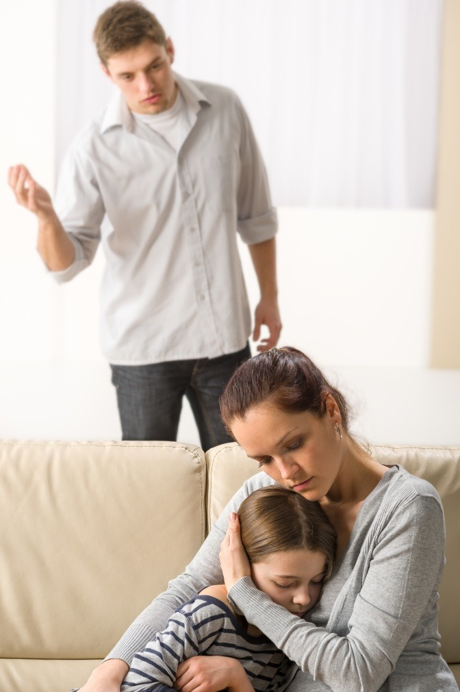 Ein Mann schreit mit einer Frau, sieh hält dem Kind die Ohren zu