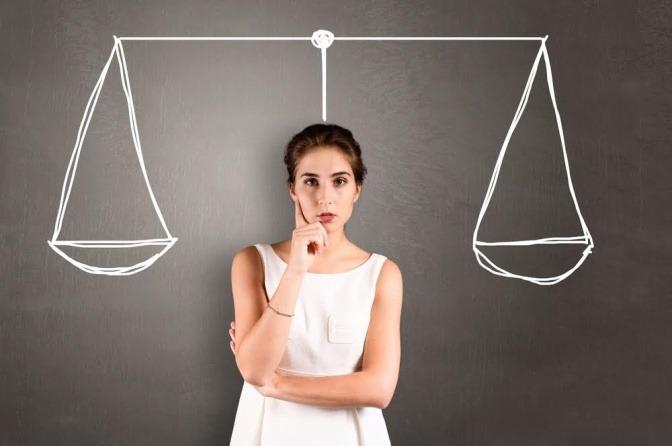 Eine Frau steht fragend vor einer Schiefertafel. Über ihr ist eine ausgeglichene Waage.