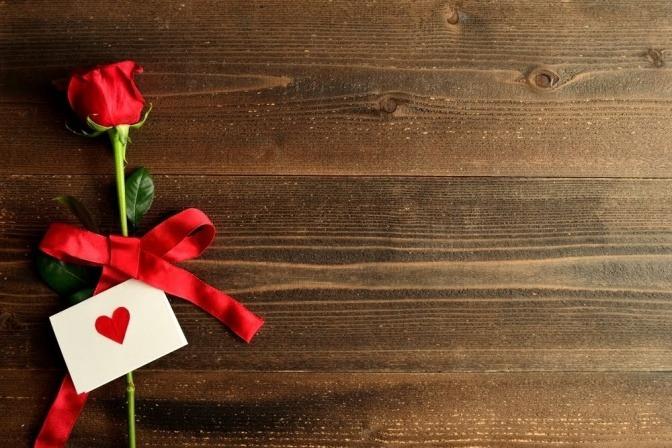 Ein kleiner Brief liegt mit einer roten Rose auf einem Holztisch.
