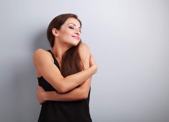 Eine Frau umarmt sich selber und lächelt dabei, ihre Augen sind geschlossen.