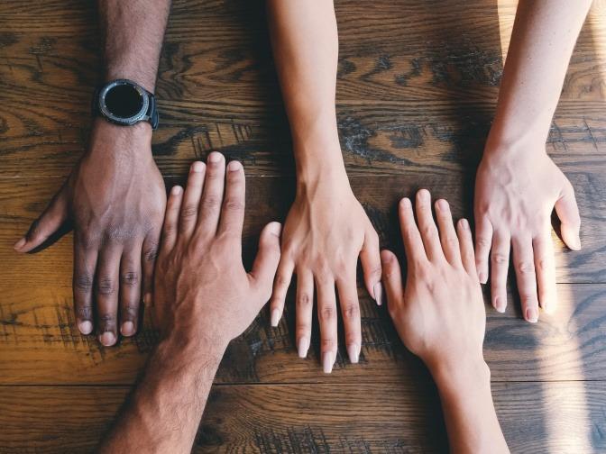Fünf Menschen haben ihre linken Hände nebeneinander auf einen Tisch gelegt.