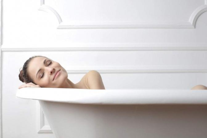 Eine Frau liegt in der Badewanne. Sie hat die Augen geschlossen, ihr Kopf liegt auf dem Seitenrand und sie wirkt zufrieden und entspannt.