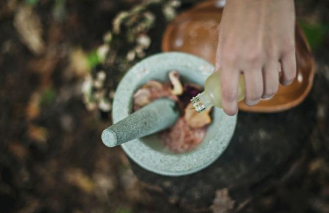 In einem Mörser werden Gewürze, Kräuter und andere Zutaten miteinander vermengt