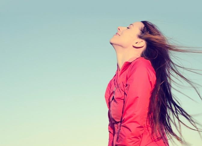 Eine junge Frau lächelt glücklich, während sie ihre Augen schließt.