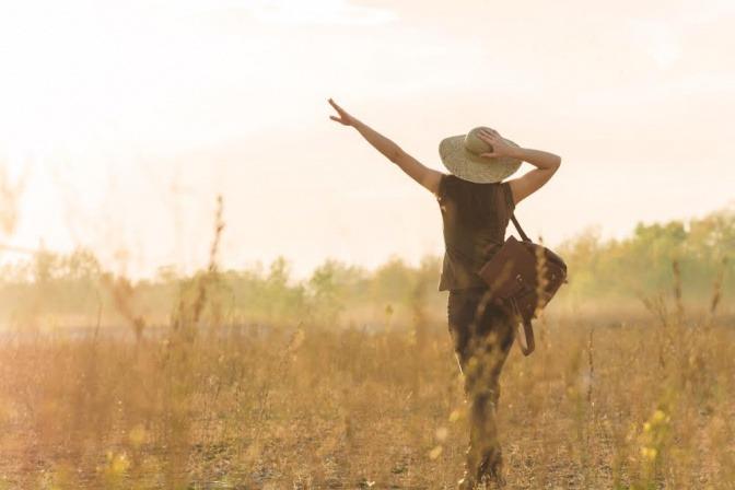 Eine Frau geht motiviert durch hohes Gras