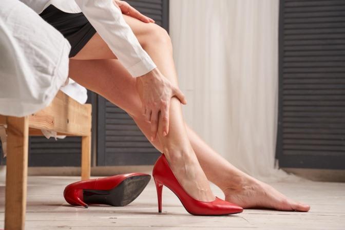 Frau in Stilettos reibt sich schwere Beine im Sommer