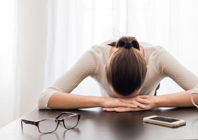 Eine Frau sitzt energielos beim Schreibtisch
