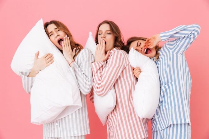 Drei junge Frauen mit Polster und Pyjama