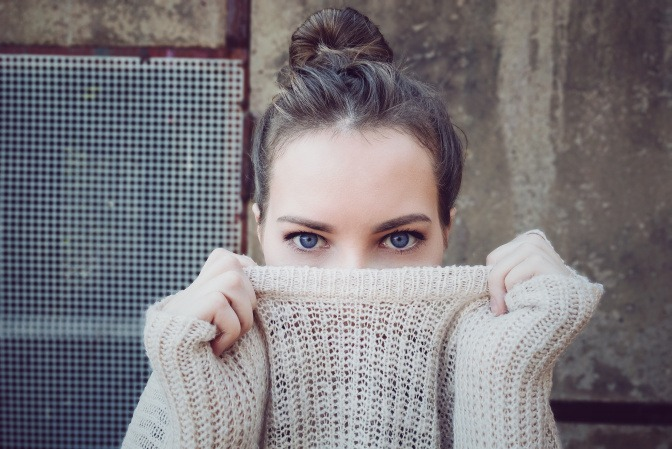 Frau riecht an ihrem Pullover