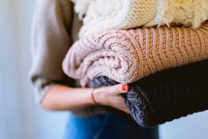 Frau mit einem Stapel Pullover im Arm
