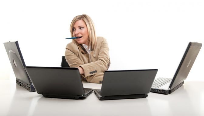 Eine Frau arbeitet multitasking an mehreren Computern