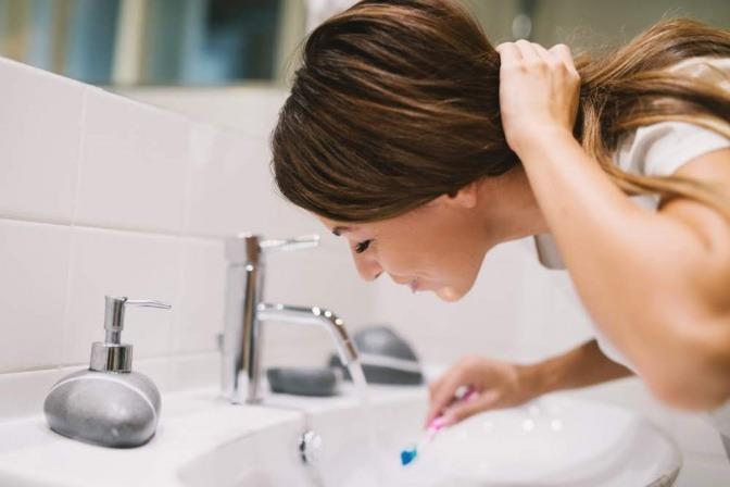 Eine Frau putzt die Zähne für ihre Mundhygiene