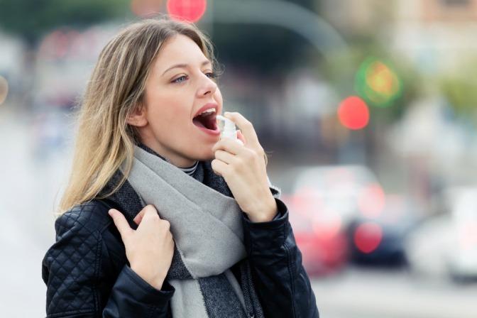 Eine Frau verwendet Mundspray gegen Viren und Bakterien