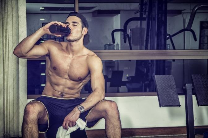 Trainierter Mann trinkt aus einer Flasche
