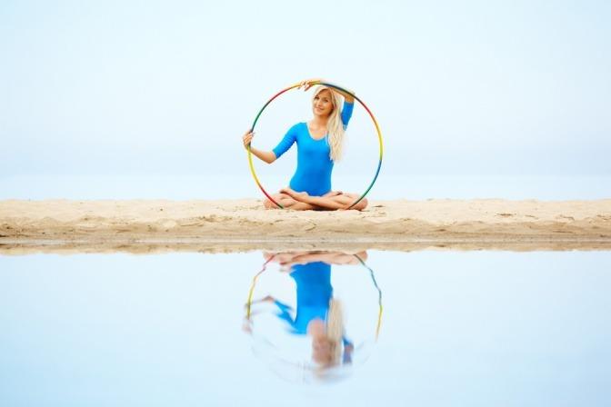 Frau im Yogasitz mit Hula Hoop Reifen