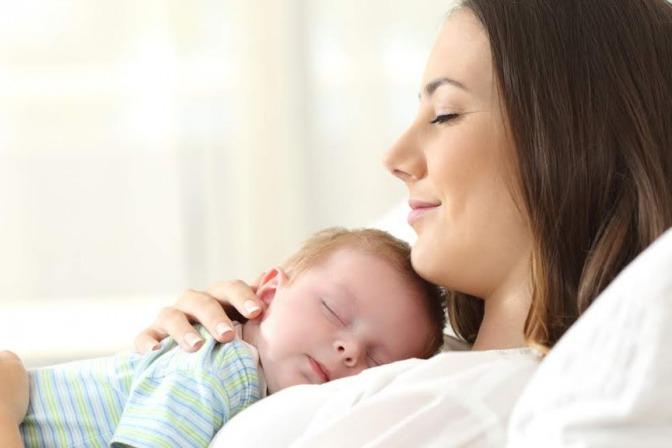 Eine junge Mutter kuschelt mit ihrem Kind