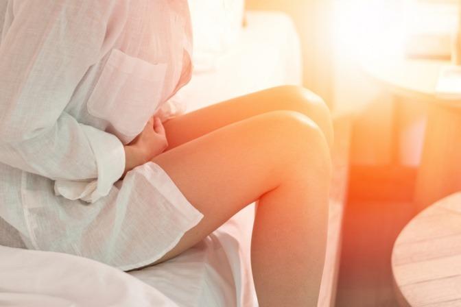 Frau mit Myomen hält sich vor Schmerzen den Unterleib