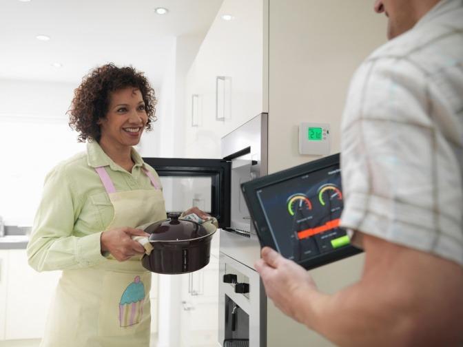 Eine Frau kocht eine Mahlzeit für die Familie, während ihr Mann den Energieverbrauch mit einem Tablet live überwacht.