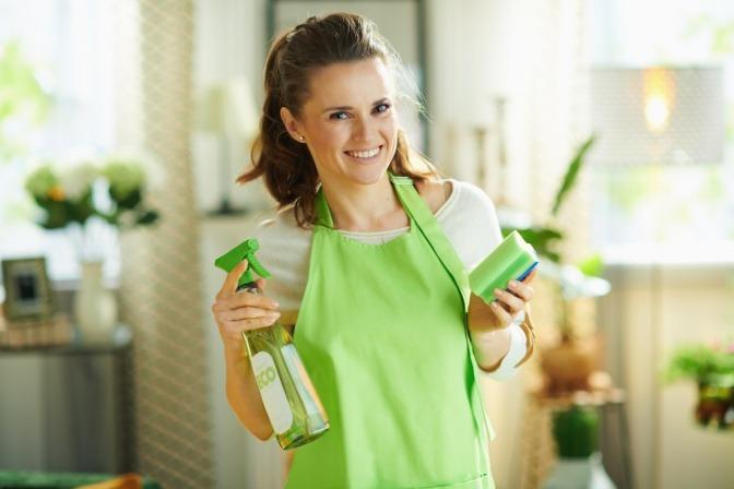 Eine lächelnde Frau hält ihr selbstgemachtes Reinigungsmittel für die Küche hoch.
