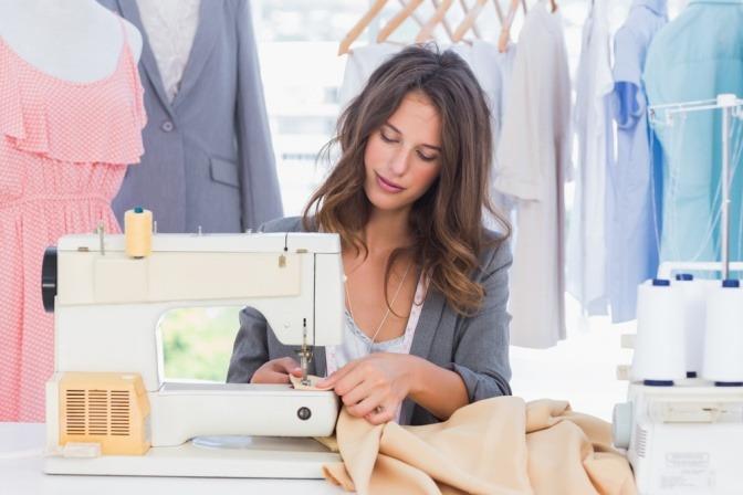 Eine Frau sitzt bei der Nähmaschine und näht