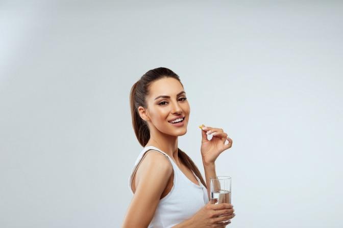 Eine Frau nimmt Nahrungsergänzungsmittel für gutes Haarwachstum