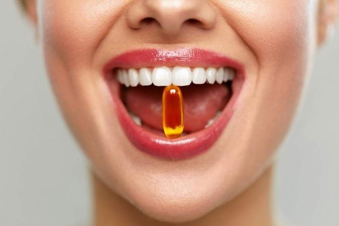 Eine Frau hat ein Nahrungsergänzungsmittel im Mund