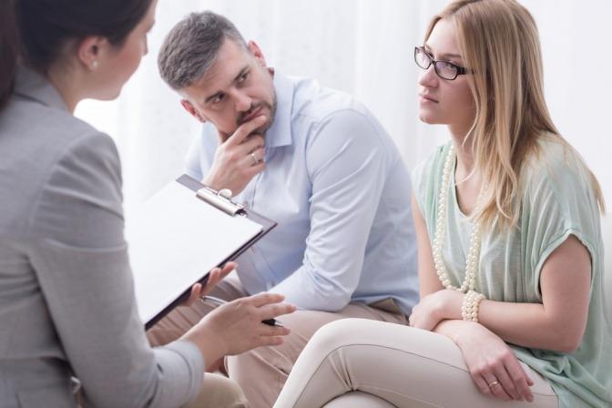 Eine verärgerte Frau spricht mit einer weiblichen Psychologin, ihr Mann blickt vorwurfsvoll zu seiner Partnerin.