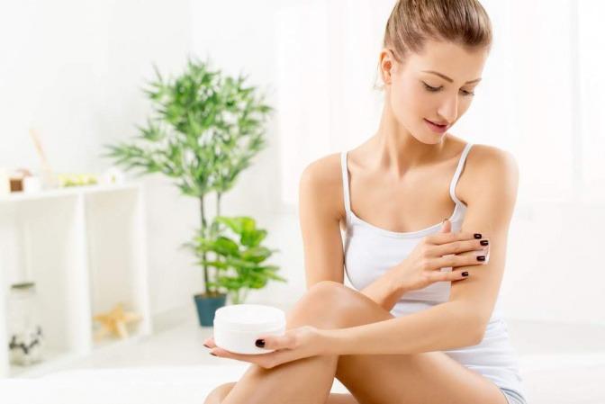 Eine Frau gibt sich natürliche Hautpflege auf den Körper