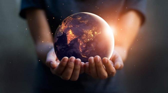 In zwei ausgestreckten Händen liegt eine Miniaturversion des Planeten Erde.  Das Modell glüht und scheint kleine Lichtblitze auszustrahlen, welche die Schwingungen der Natur symbolisieren sollen.
