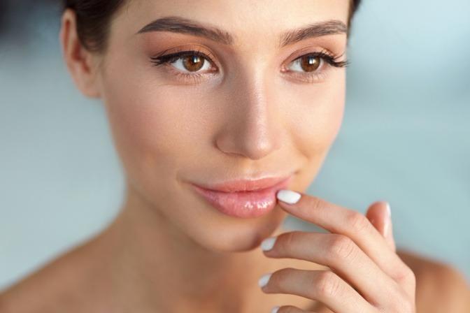Eine Frau trägt natürliches Make-up und weißen Nagellack