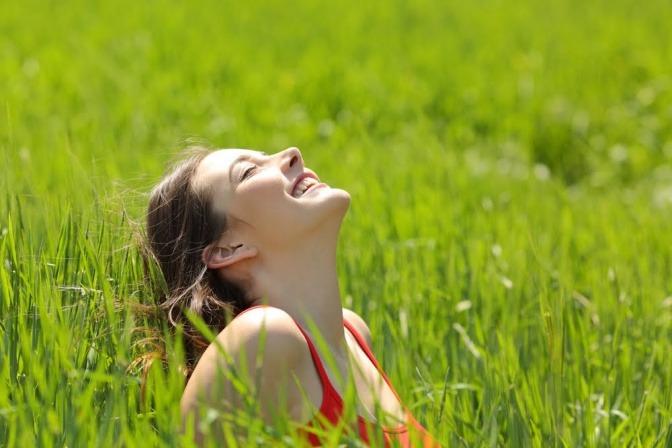 Eine Frau sitzt auf einer Wiese mit hohem Gras und lächelt gen Himmel.