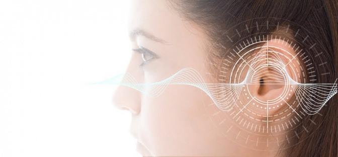 Der Kopf einer jungen Frau im Profil. Über ihr linkes Ohr ist eine Zeichnung eines Frequenzmuster gelegt, das in der Mitte, gleich über ihrem Hörkanal, deutlich nach oben ausschlägt.