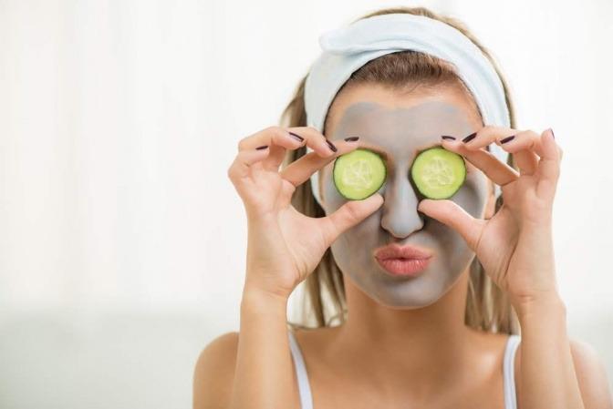 Eine Frau hat sich eine Gesichtsmaske aus organischen Kosmetikprodukten gemacht. Sie hält mit ihren Händen je eine Gurkenscheibe auf ihren Augen fixiert.