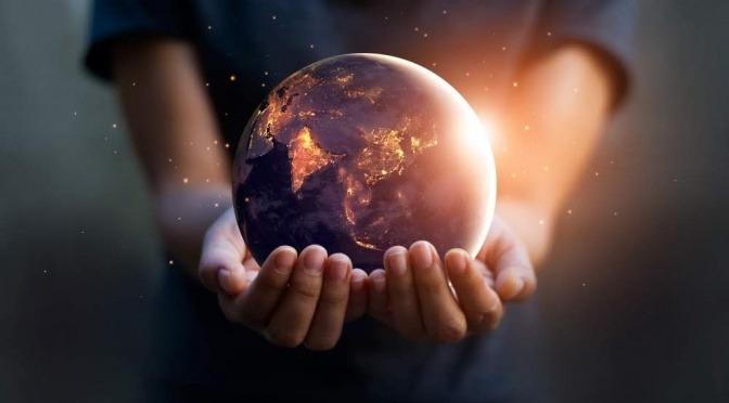 Eine Frau hält eine kleine leuchtende Kugel in der Hand, die der Erde gleicht.