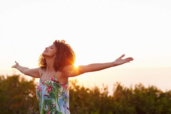 Eine Frau steht beim Sonnenaufgang mit ausgebreiteten Armen auf einem Feld und atmet tief ein.