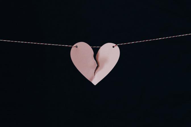 Ein eingerissenes Herz aus Papier hängt aufgespannt an einer Kordel.