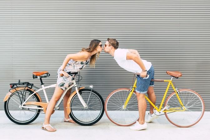 Ein Mann und eine Frau am Fahrrad küssen sich