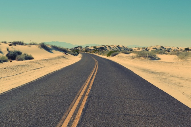 Eine leere Straße in einer Wüstenumgebung symbolisiert die Wichtigkeit von Distanz, um erfolgreich einen Neuanfang nach Trennung oder Scheidung zu vollziehen.