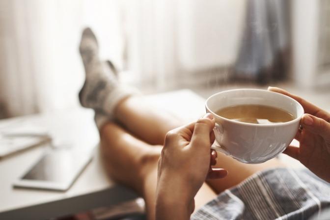 Frau entspannt mit Tee auf dem Sofa.