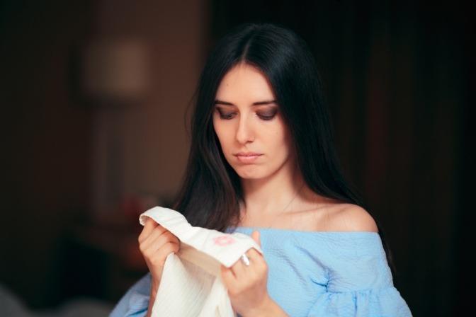 Eine Frau blickt sehnsuchtsvoll auf ein getragenes Hemd eines Mannes mit einem Lippenstiftabdruck am Kragen.